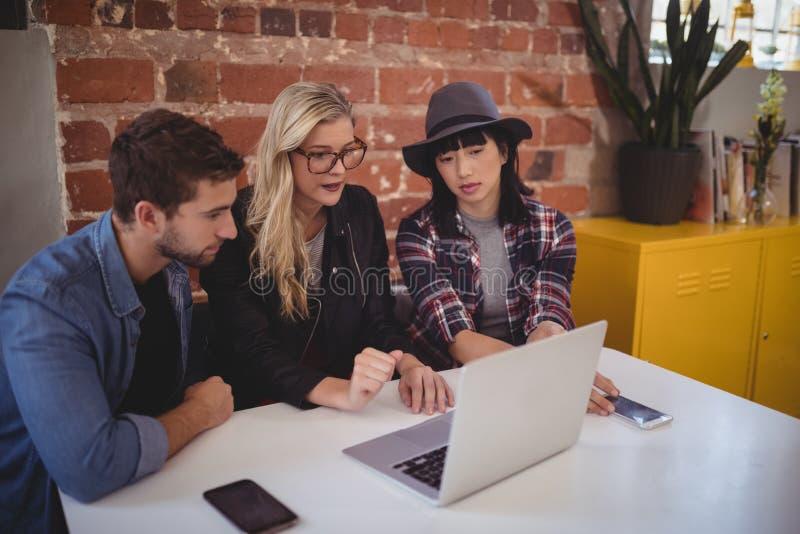 Giovane gruppo creativo facendo uso del computer portatile mentre sedendosi alla caffetteria immagine stock
