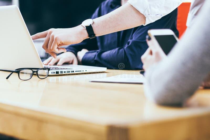 Giovane gruppo di affari al tavolo di riunione con i dispositivi astuti fotografie stock
