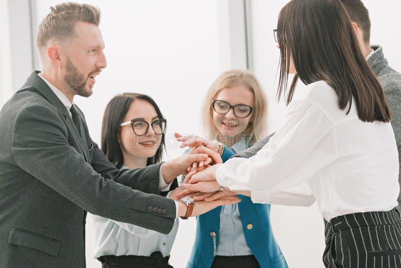 Giovane gruppo di affari che unisce insieme le loro mani fotografie stock