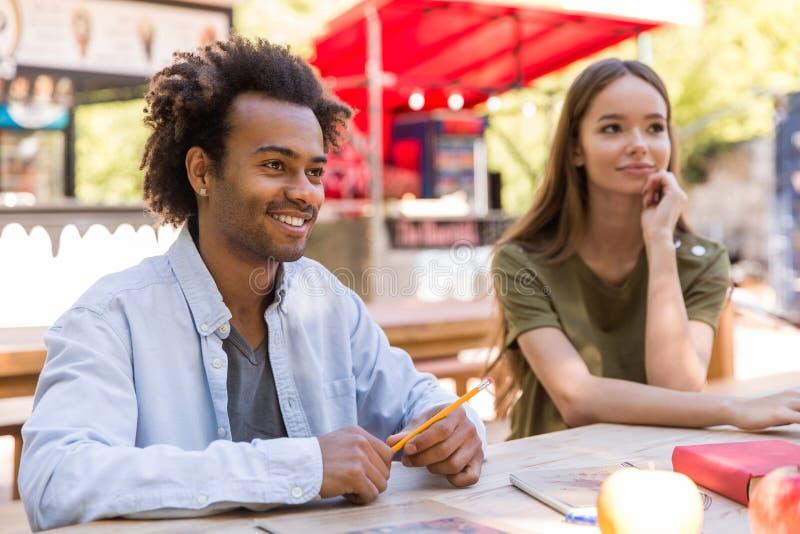 Giovane gruppo multietnico allegro di conversazione degli studenti degli amici fotografia stock