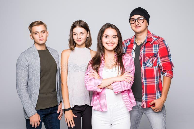 Giovane gruppo sorridente felice di amici che stanno isolato insieme su bianco fotografia stock libera da diritti