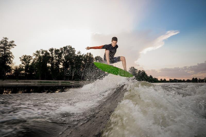 Giovane guida attraente dell'uomo sul wakeboard sui precedenti o immagini stock libere da diritti