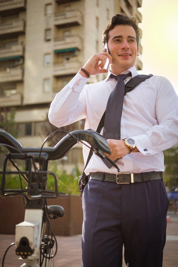 Giovane guida di buinessman da lavorare nella città fotografia stock