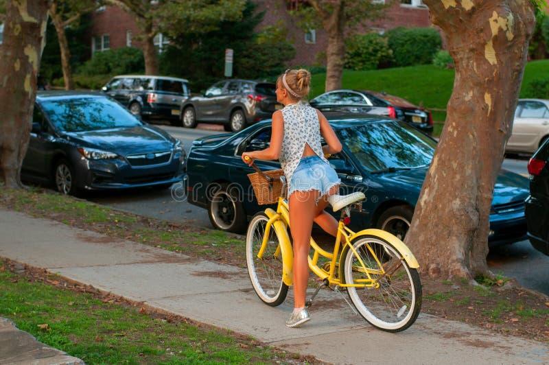 Giovane guida felice del ciclista nella città fotografia stock
