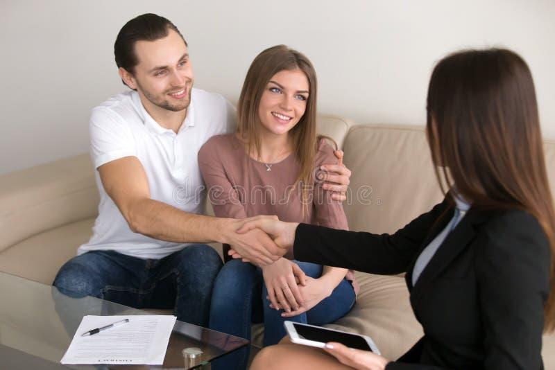 Giovane handshake felice del responsabile del mediatore e delle coppie dopo la firma fotografia stock libera da diritti
