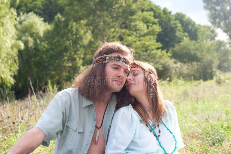 Giovane hippy delle coppie sul prato immagine stock libera da diritti