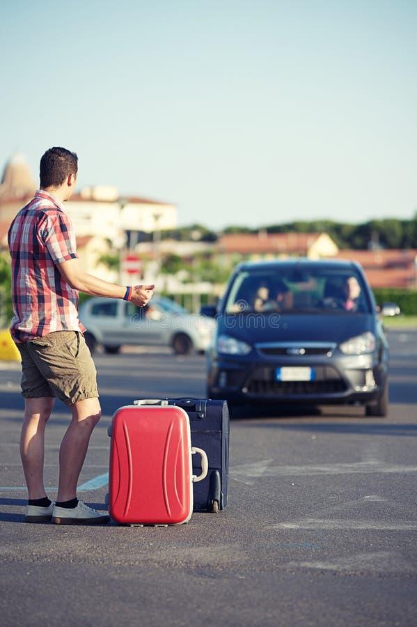 Giovane hitchhiker sulla via della città immagini stock libere da diritti