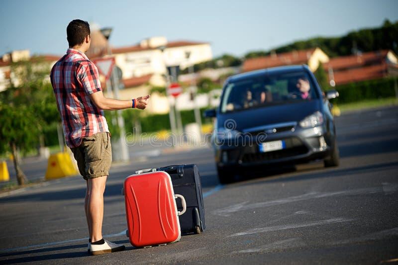 Giovane hitchhiker sulla via della città immagini stock