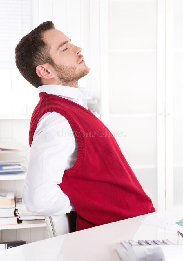 Giovane impiegato bello con il mal di schiena all'ufficio. immagine stock