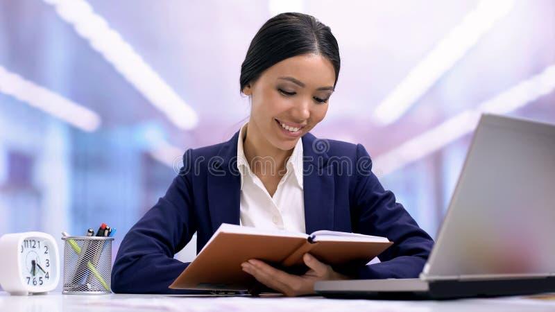 Giovane impiegato femminile che scrive in taccuino, giorno del lavoro di pianificazione, idee, disciplina immagini stock
