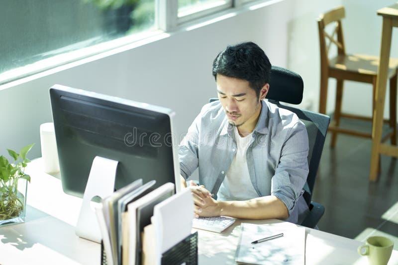 Giovane imprenditore asiatico che contempla nell'ufficio fotografia stock