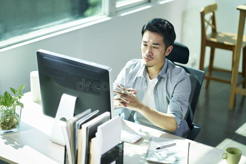 Giovane imprenditore asiatico che contempla nell'ufficio immagine stock