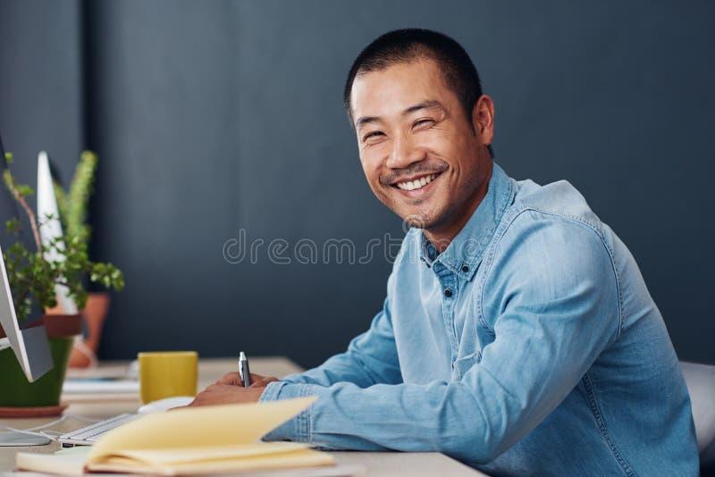 Giovane imprenditore asiatico sorridente che lavora alla sua scrivania immagine stock