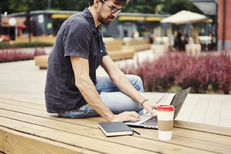 Giovane imprenditore che lavora al parco fuori sul banco di legno Giovane imprenditore che lavora al parco fuori sul banco di leg fotografia stock