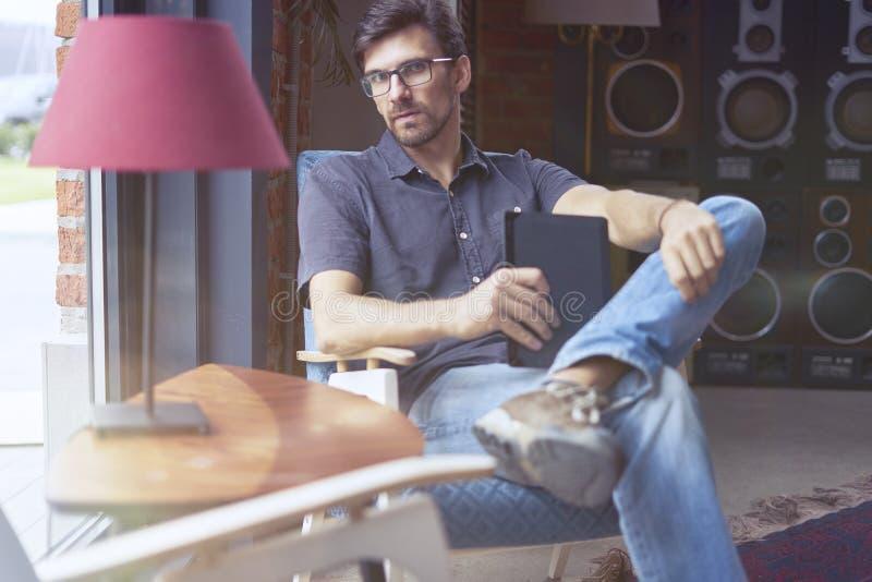 Giovane imprenditore che lavora alla partenza in ufficio moderno facendo uso della compressa digitale Equipaggi i vetri ed i jean immagini stock