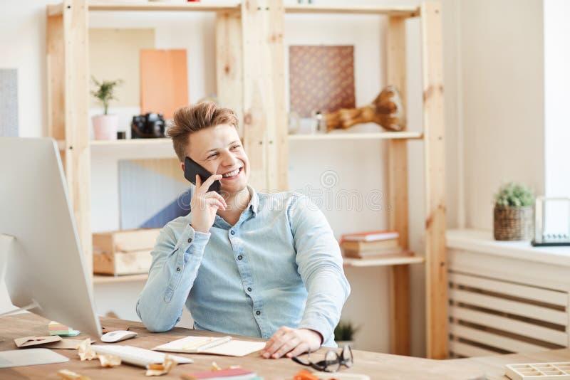 Giovane imprenditore positivo che discute progetto sul telefono immagini stock