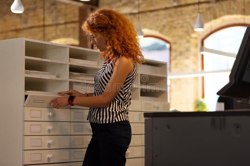 Giovane imprenditrice coi capelli rossi vicino al cassetto fotografia stock libera da diritti
