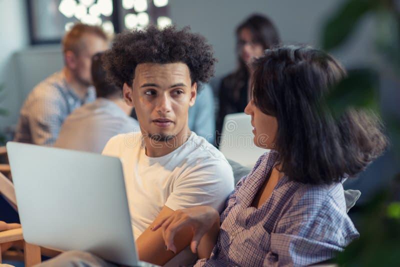 Giovane impresa e nuovo concetto mobile di tecnologia con le giovani coppie multietniche nell'interno luminoso moderno dell'uffic immagine stock libera da diritti
