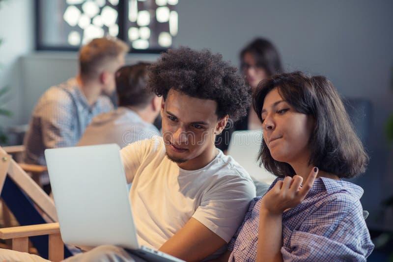 Giovane impresa e nuovo concetto mobile di tecnologia con le giovani coppie multietniche nell'interno luminoso moderno dell'uffic fotografie stock libere da diritti