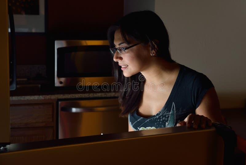 Giovane incursione ispana del frigorifero di notte della donna a casa - immagine stock libera da diritti