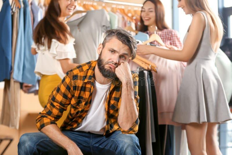 Giovane infastidito che aspetta la sua amica ed i suoi amici mentre essi che scelgono i vestiti in negozio fotografie stock libere da diritti