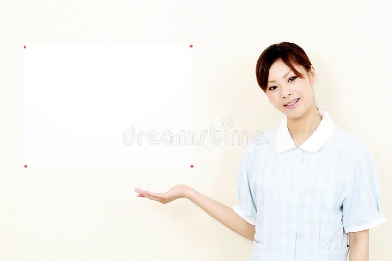 Giovane infermiera sorridente graziosa che lo accoglie favorevolmente immagini stock libere da diritti