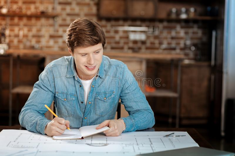 Giovane ingegnere allegro che fa i calcoli per il suo progetto fotografia stock libera da diritti
