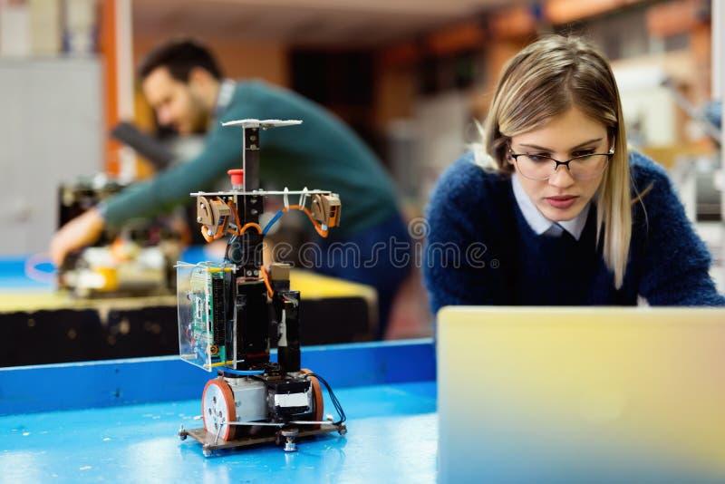Giovane ingegnere che collauda il suo robot in officina fotografia stock libera da diritti