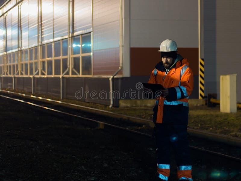 Giovane ingegnere che lavora durante i otdoors dello spostamento del hignt in casco immagini stock