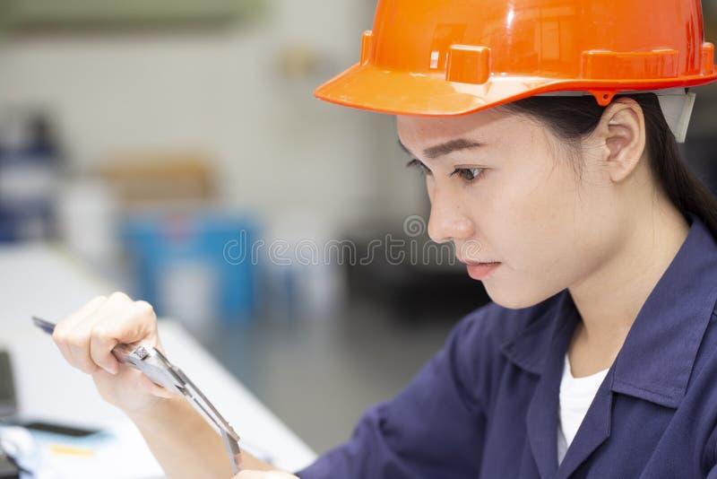 Giovane ingegnere facendo uso del verniero in laboratorio il concpet di ricerca immagini stock libere da diritti