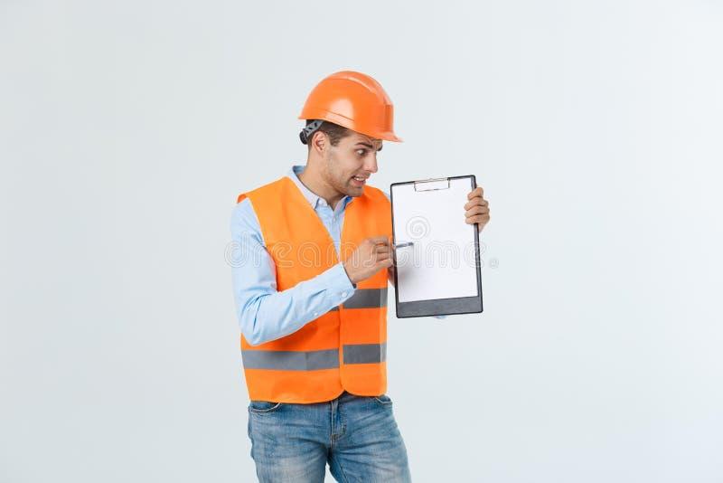 Giovane ingegnere frustrato con l'elmetto protettivo e la maglia riflettente che verifica l'errore nel documento sopra fondo grig fotografia stock libera da diritti