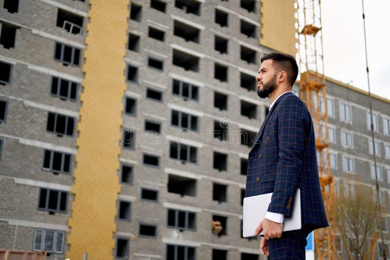 Giovane ingegnere o architetto che lavora con il computer portatile a al cantiere Concetti della costruzione di edifici e di inge fotografie stock