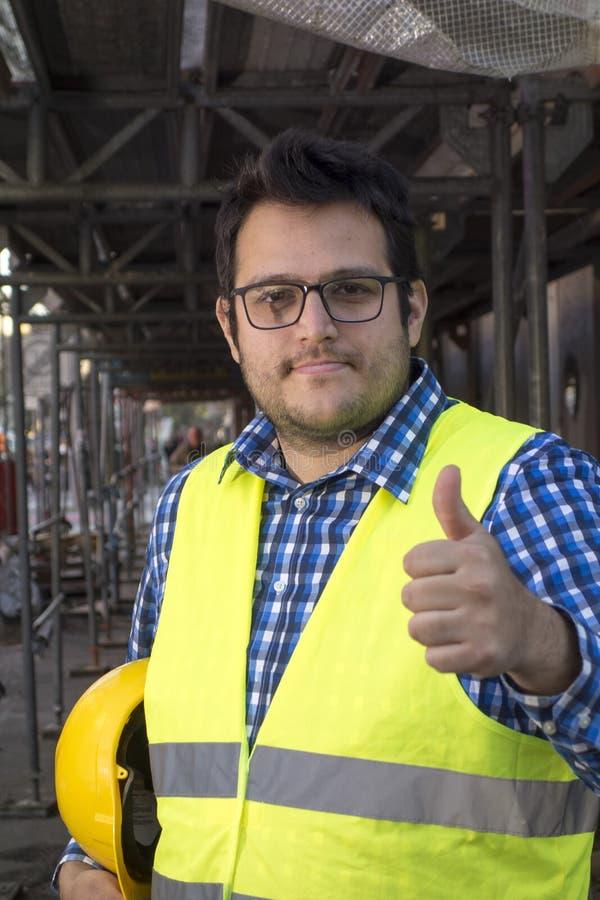 Giovane ingegnere in posa con i pollici in alto immagini stock