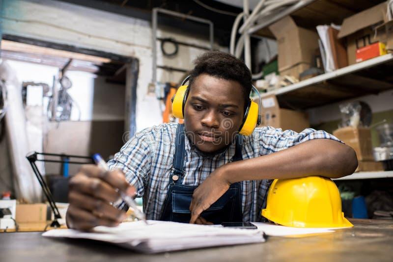 Giovane ingegnere premuroso che lavora nella stanza scura fotografie stock libere da diritti