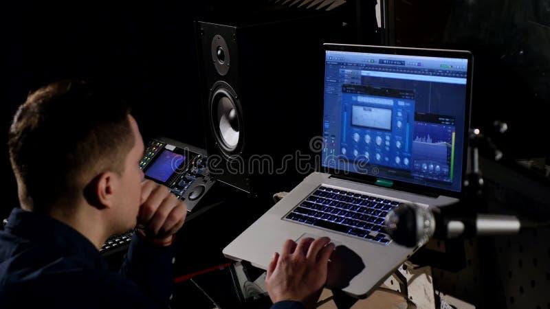 giovane ingegnere sano 4K in studio di registrazione facendo uso del computer portatile allo scrittorio di miscelazione immagini stock