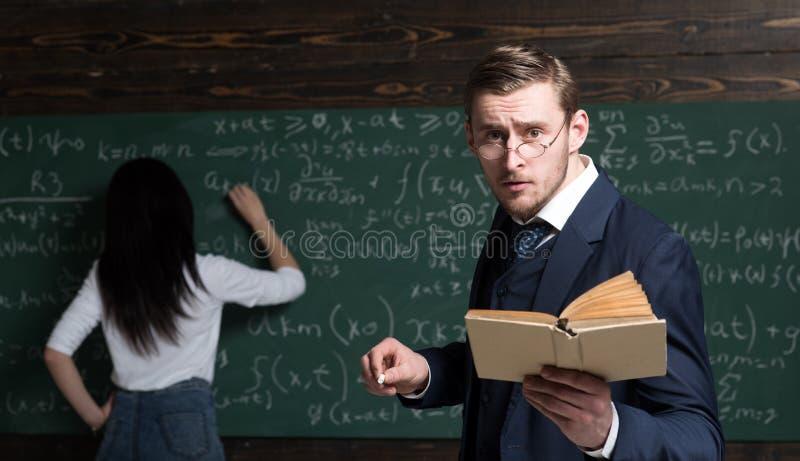 Giovane insegnante agitato con il sembrare ansioso che sta nell'aula con il libro e nel gesso in sue mani Giovane studente fotografia stock