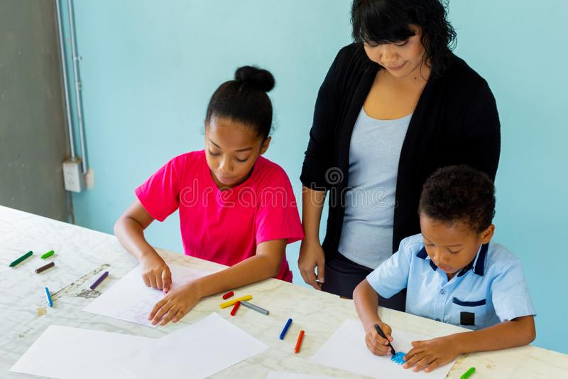 Giovane insegnante che d? a bambini afroamericani una lezione di arte e che insegna a come disegnare fotografia stock