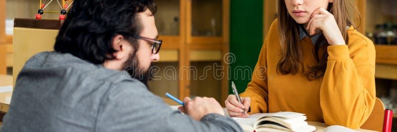 Giovane insegnante ispanico maschio che aiuta il suo studente nella classe di chimica Concetto di istruzione, di ripetizioni e di fotografia stock