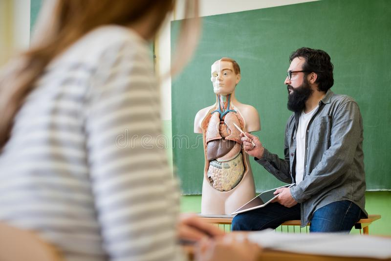 Giovane insegnante ispanico maschio nella classe di Biologia, tenente compressa digitale e d'istruzione all'anatomia del corpo um fotografia stock