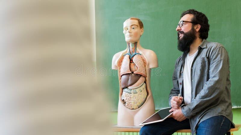 Giovane insegnante ispanico maschio nella classe di Biologia, tenente compressa digitale e d'istruzione all'anatomia del corpo um fotografie stock