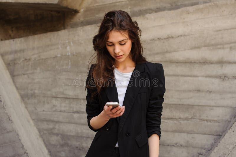 Giovane invio di messaggi di testo caucasico della ragazza che esamina il telefono fotografia stock libera da diritti