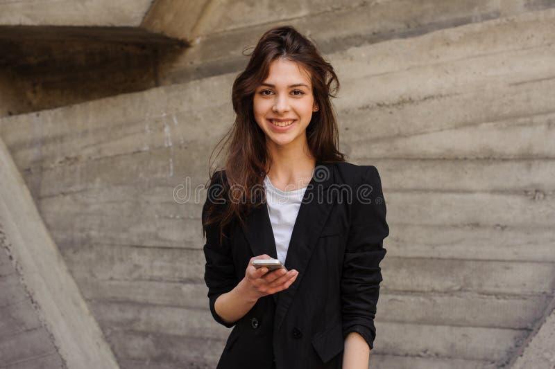 Giovane invio di messaggi di testo caucasico della ragazza che esamina la macchina fotografica immagine stock libera da diritti