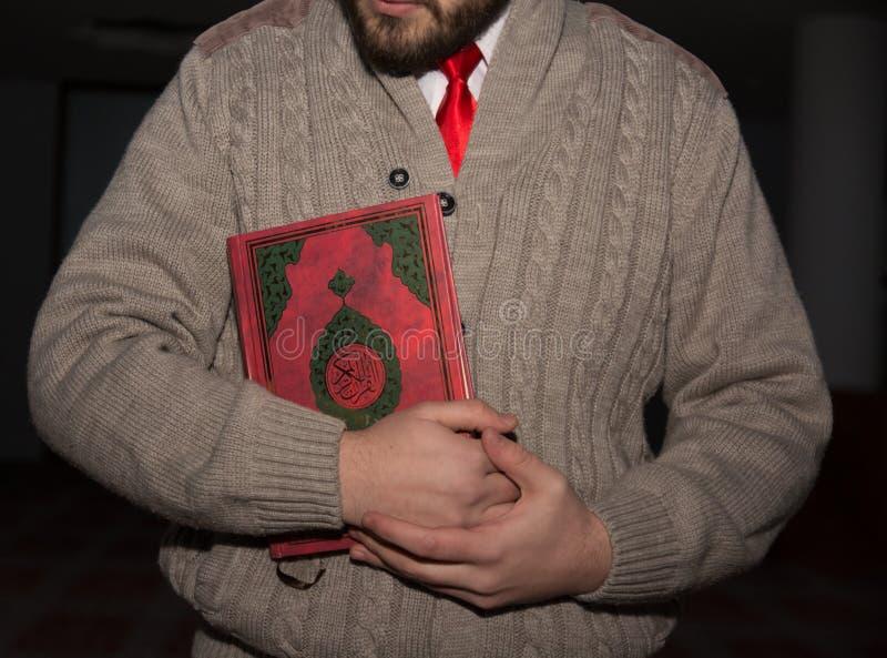 Giovane koran musulmano della tenuta dell'uomo in mani immagini stock libere da diritti