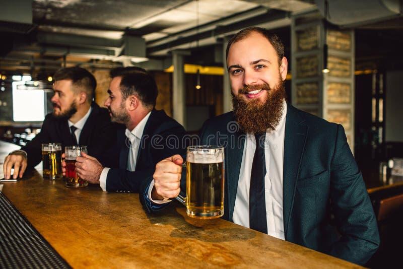 Giovane l'uomo d'affari positivo e felice si siede al contatore della barra Sorride sulla macchina fotografica Tazza di birra del fotografie stock libere da diritti