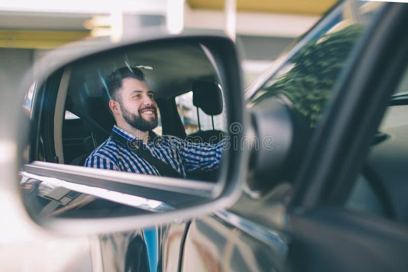 Giovane l'uomo serio elegante moro e barbuto bello conduce un'automobile immagini stock