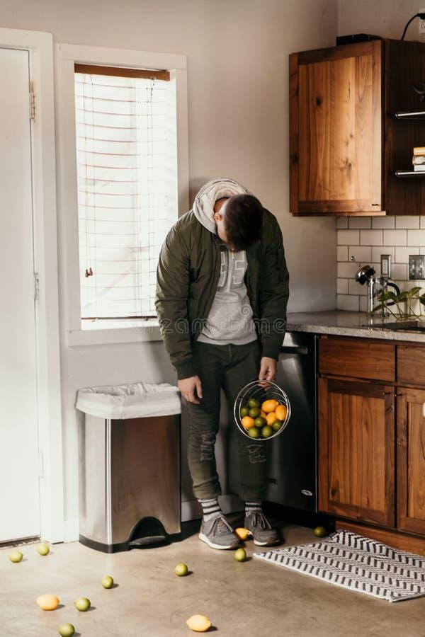 Giovane la persona adulta turbata e sconfigguta rovescia casualmente il canestro dei limoni e della frutta della calce da ogni pa fotografia stock libera da diritti
