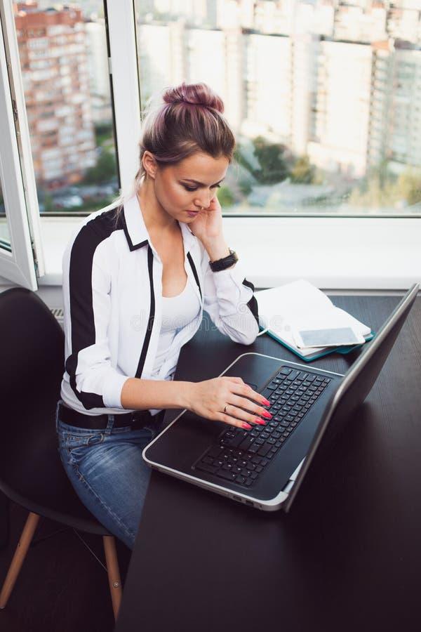 Giovane lavorare biondo ad un computer portatile Ragazza in ufficio moderno immagine stock libera da diritti