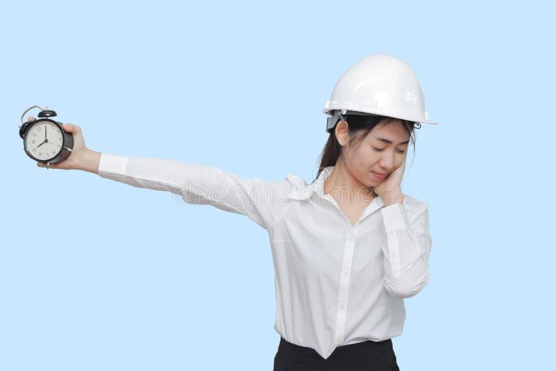 Giovane lavoratore asiatico attraente con la sveglia della tenuta dell'attrezzatura di sicurezza su fondo isolato blu immagine stock libera da diritti