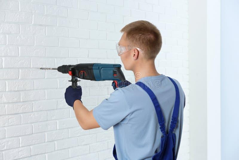 Giovane lavoratore bello che per mezzo del martello rotatorio Riparazione domestica immagine stock