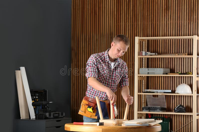 Giovane lavoratore bello che ripara panchetto di legno facendo uso del cacciavite fotografia stock